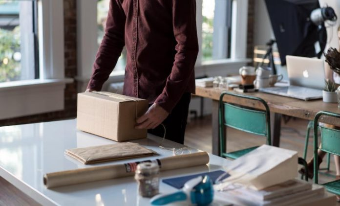 a man is packing drop shipping sale order